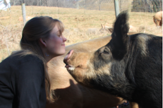 My wife giving one of our pastured pigs a kiss