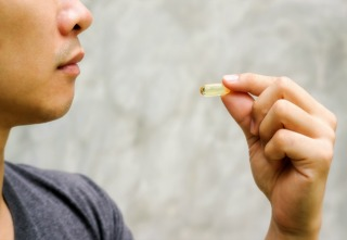Close up of a man take a fish oil capsule.