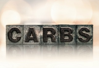 """The word """"CARBS"""" written in vintage ink stained letterpress type."""
