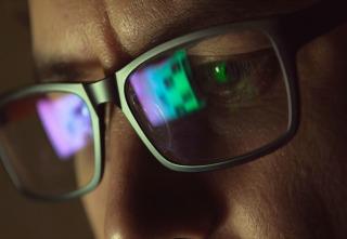Reflection at eyeglasses of man: looking at a website